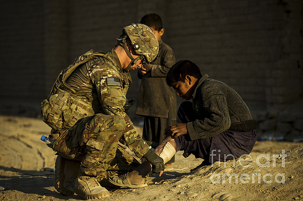 Air Force Photograph - Airman Provides Medical Aid To A Local by Stocktrek Images