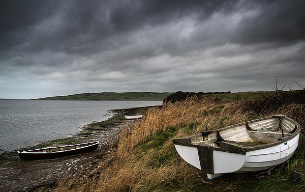 Boat Photograph - Old Decayed Rowing Boats On Shore Of Lake With Stormy Sky Overhe by Matthew Gibson