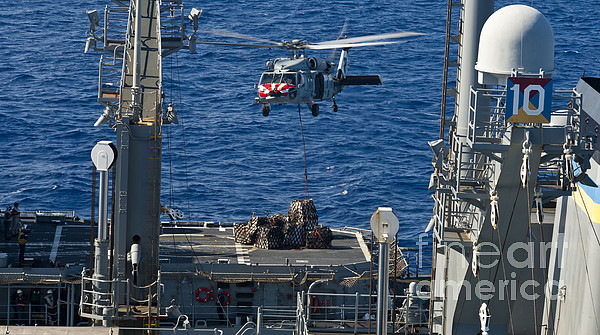 Military Photograph - An Mh-60s Sea Hawk Delivers Supplies by Stocktrek Images