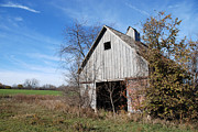 Ramshackle Prints - An old rundown abandoned wooden barn under a blue sky in midwestern Illinois USA Print by Paul Velgos