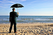 Getting Away From It All Posters - Businessman with umbrella on beach Poster by Sami Sarkis