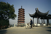Baskets Photos - A Man Cycles Past A Pagoda by Justin Guariglia