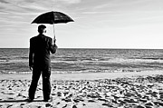 Out Of Context Posters - Businessman with umbrella on beach Poster by Sami Sarkis