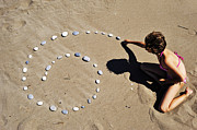 Sami Sarkis - Girl on beach displaying pebbles in...