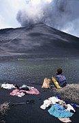 {locations} Posters - Girl washing clothes in a lake with the Mount Yasur volcano emitting smoke in the background Poster by Sami Sarkis