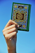 Koran Framed Prints - Hand holding the Koran book Framed Print by Sami Sarkis