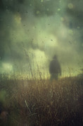 Gloomy Posters - Hooded man walking in field with storm clouds Poster by Sandra Cunningham