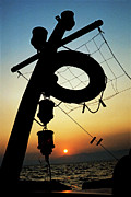 Fishing Boats Framed Prints - Lifebuoy silhouetted on a fishing boat at sunset Framed Print by Sami Sarkis