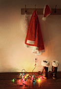 Hook Posters - Santa costume hanging on coat hook with christmas lights Poster by Sandra Cunningham