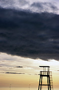 Dramatic Skies Framed Prints - Storm clouds gathering over a lifeguard tower at sunset Framed Print by Sami Sarkis
