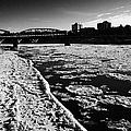 large chunks of floating ice on the south saskatchewan river in winter flowing through downtown Sask by Joe Fox