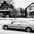 car covered in snow parked by the side of the street in front of residential homes caswell hill Sask by Joe Fox