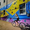 Girl Rides Bicycle Past Mural On The South Side Of Pittsburgh by Amy Cicconi