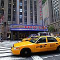 Yellow Cabs Pass In Front Of Radio City Music Hall by Amy Cicconi