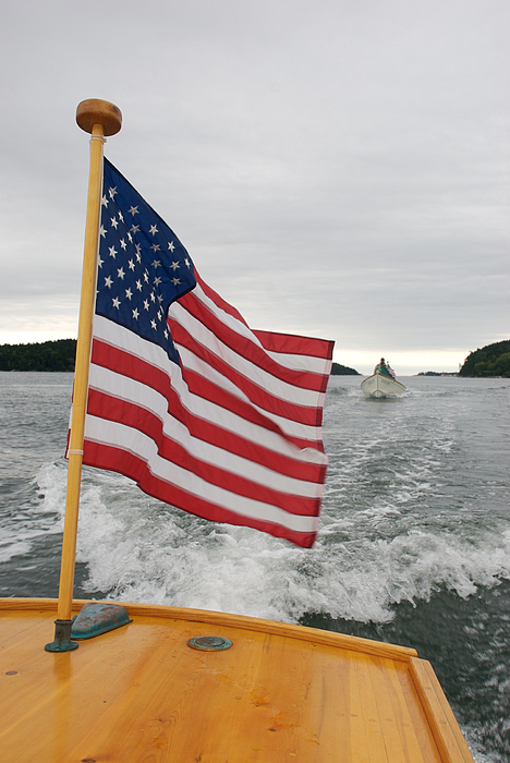 Nobody Photograph - A Flag Waves On The Stern Of A Maine by Heather Perry