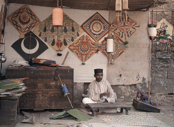 Day Photograph - A Kite Merchant Sits In His Store by Gervais Courtellemont