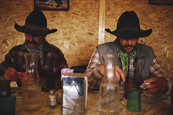 Model Released Photography Photograph - A Pair Of Cowboys Enjoy A Cup Of Coffee by Joel Sartore