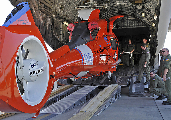 Ramp Photograph - An Aircrew Loads A Coast Guard Hh-65 by Stocktrek Images