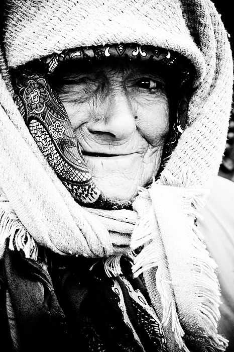 Portrait; Old; Senior; People; Female; Person; Woman; Mature; Adult; Elderly; Pensioner; Expression; Retirement; Retired; Grandmother; Face; Caucasian; Smile; White; Aged; Background; Grey; Look; Older; Wrinkle; Wrinkled; Lifestyle; Poor; Poverty; Black And White; Bw;  Photograph - Keeping Warm by Gabriela Insuratelu
