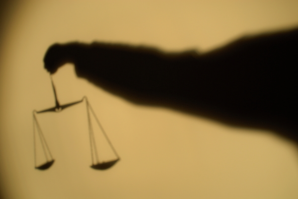 Arm Photograph - Shadow Of A Persons Arm Holding Out The Scales Of Justice by Sami Sarkis