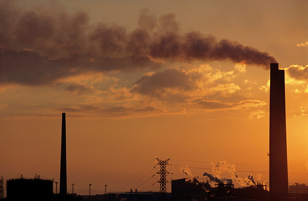 Silhouetted Smoking Chimney At Sunset Photograph