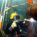 U.s. Navy Diver Welds A Repair Patch by Stocktrek Images