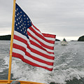A Flag Waves On The Stern Of A Maine by Heather Perry