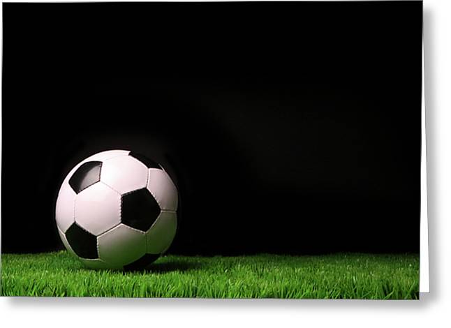 Competition Photographs Greeting Cards - Soccer ball on grass against black Greeting Card by Sandra Cunningham