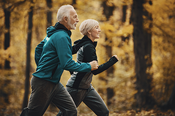Senior Couple Jogging In A Forest. Photograph by Gilaxia