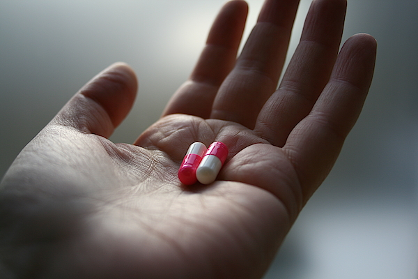 A Hand Holding Two Pills Photograph by Red Sky