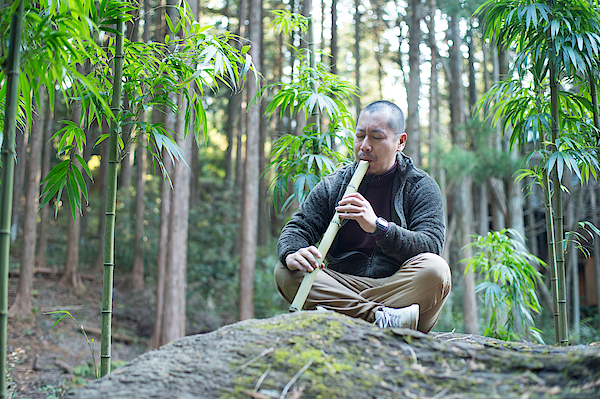 A Man Playing Bamboo Flute In The Bamboo Forest Photograph by Toshiro Shimada