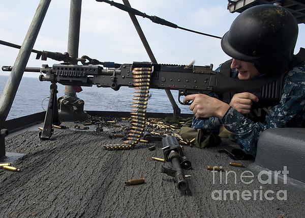 Military Photograph - A Sailor Fires An M-240b Machine Gun by Stocktrek Images