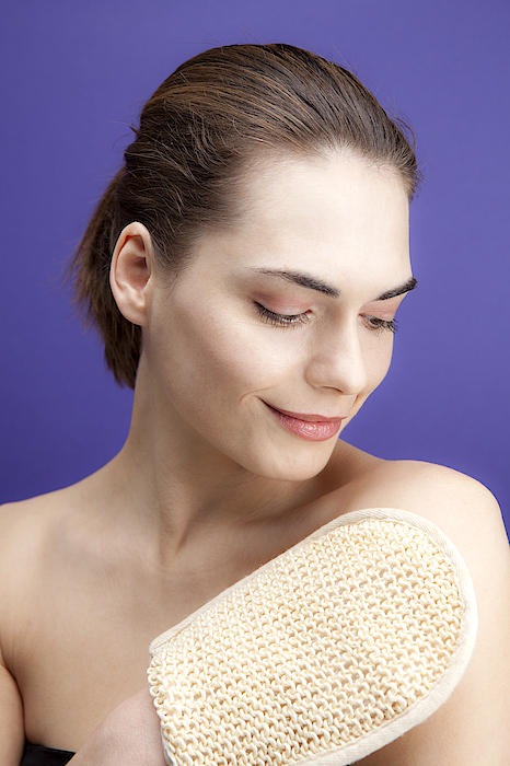 A Smiling Young Woman Using A Loofah Sponge Photograph by Halfdark
