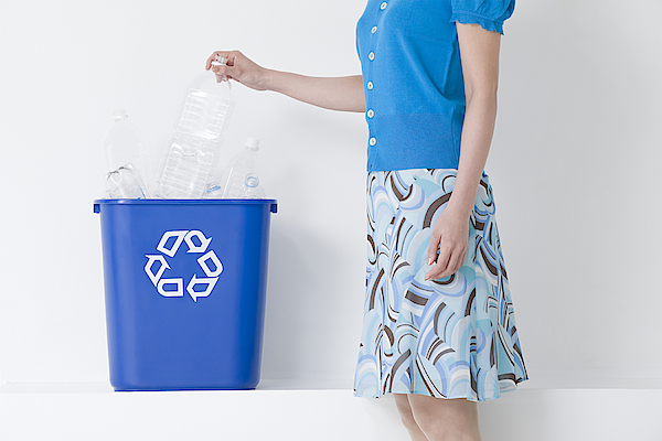 A Woman Putting A Bottle In A Recycling Bin Photograph by Image Source