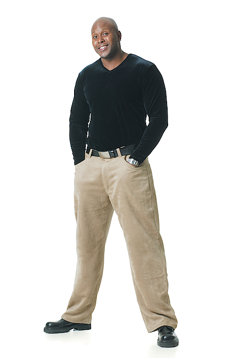 An African American Man In Tan Pants And A Black Shirt Puts His Hands In His Pockets And Smiles Photograph by Photodisc