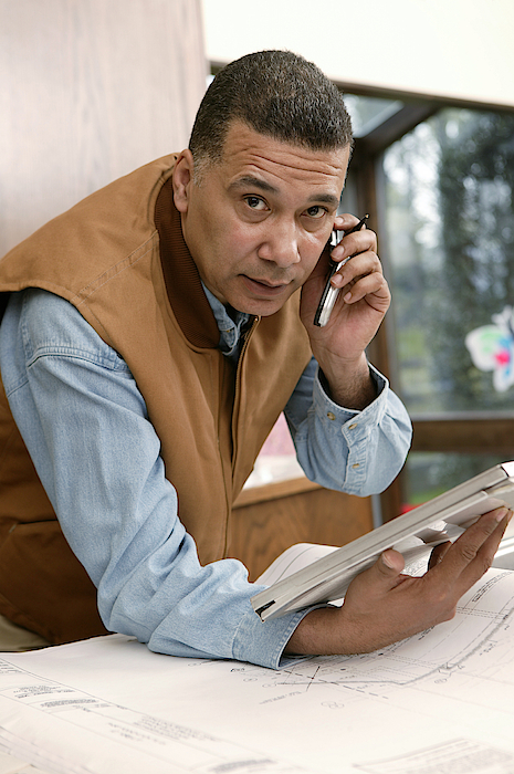 Architect Talking On Cell Phone Photograph by Comstock Images