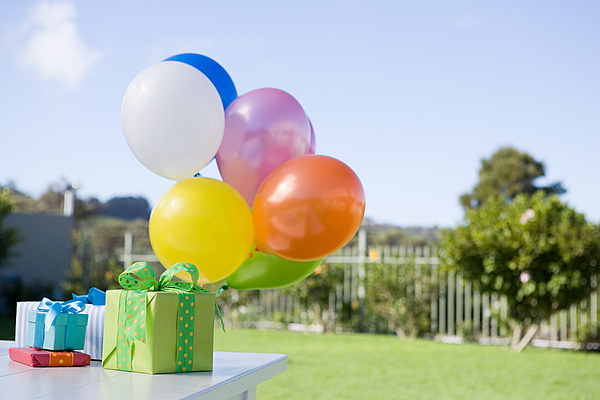 Balloons And Birthday Presents On Table In Garden Photograph by Image Source