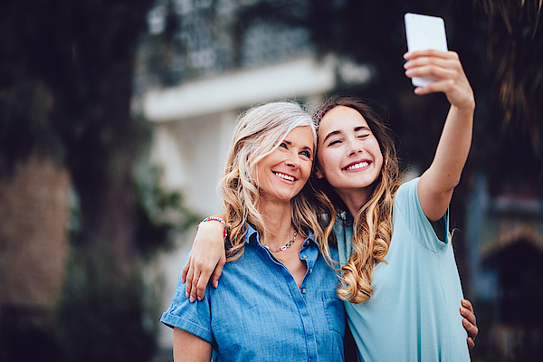 Beautiful Mature Mother And Adult Daughter Taking Selfies Together Photograph by Wundervisuals