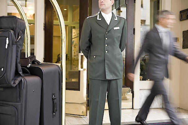 Bellhop Standing Next To Luggage Cart Photograph by UpperCut Images