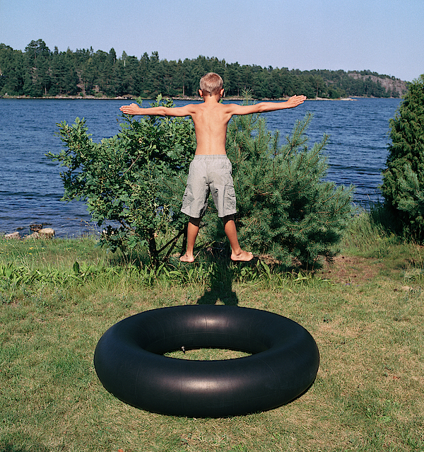 Boy (8-10) Bouncing On Large Rubber Ring, Outdoors, Rear View Photograph by Biddiboo