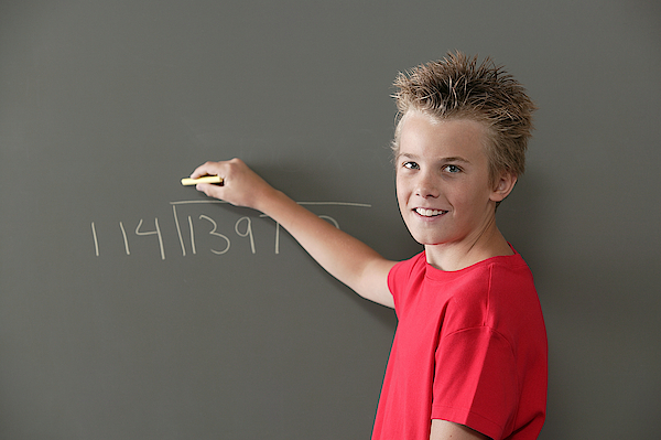 Boy Writing On Blackboard Photograph by Comstock Images
