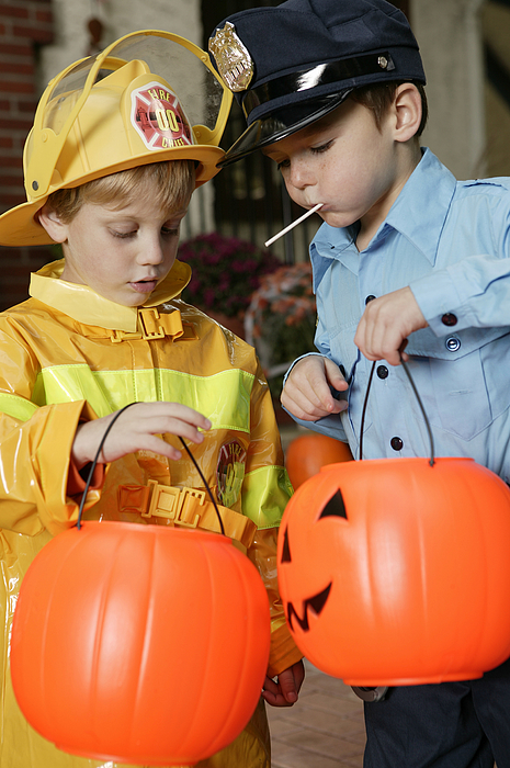 Boys In Halloween Costumes Eating Candy Photograph by Comstock Images