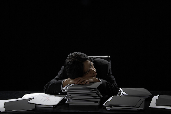 Businessman Asleep At Desk Resting Head On Stack Of Files Photograph by James Woodson