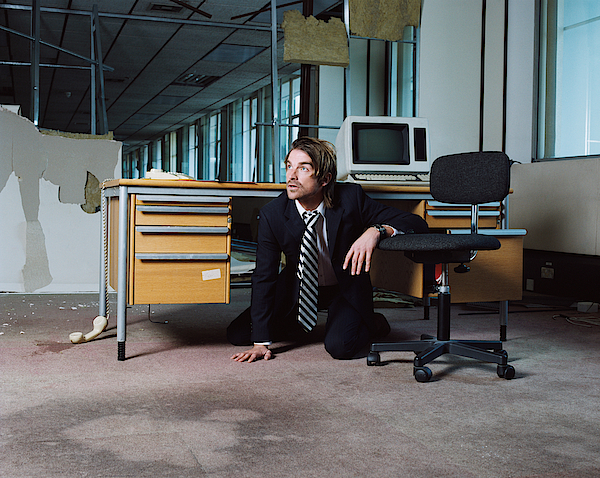 Businessman Emerging From Under Desk Photograph by Image Source