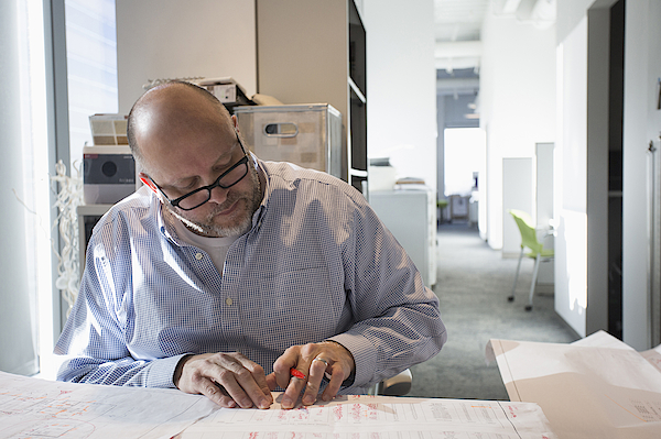 Businessman Sketching Blueprints In Office Photograph by Hill Street Studios