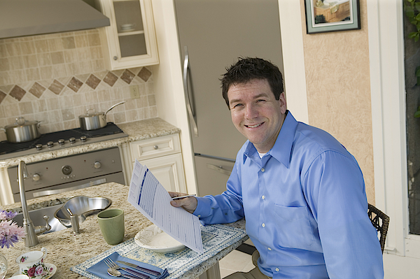 Businessman With Paperwork At Home Photograph by Comstock Images