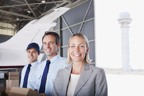 Businesswoman And Workers Standing In Hangar Photograph by Martin Barraud