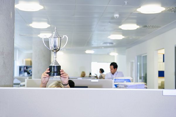 Businesswoman Holding Trophy Over Office Cubicle Photograph by Jacobs Stock Photography Ltd