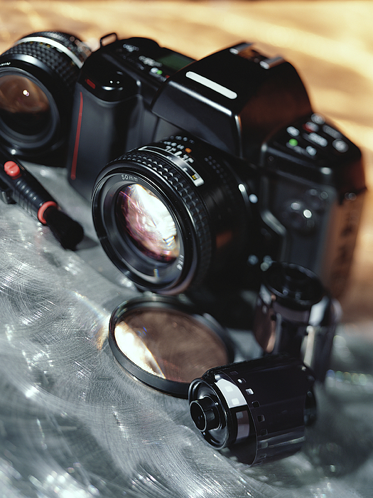Camera, Lenses, And Film Canister Photograph by Stockbyte