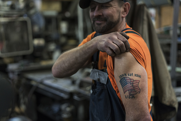 Caucasian Worker Displaying Tattoo In Factory Photograph by Jetta Productions Inc